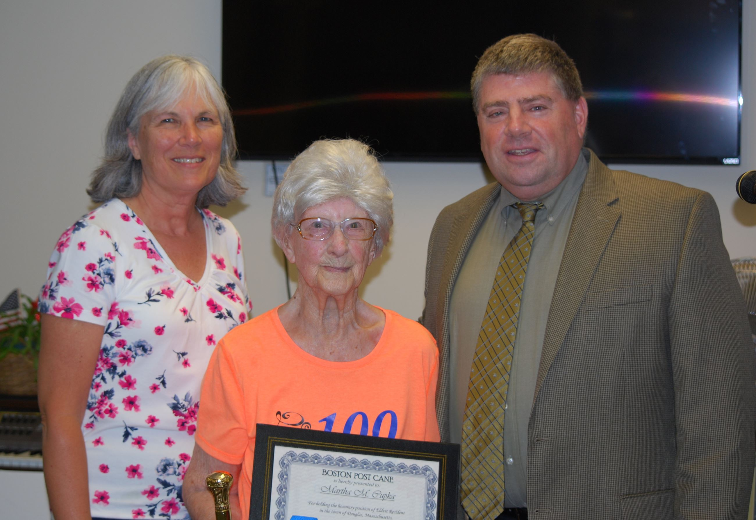 Selectman Cortese, and Suzanne Kane, present Boston Post Cane certificate to Martha Chupka