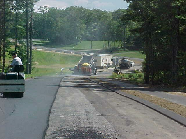 Image of work trucks paving a road